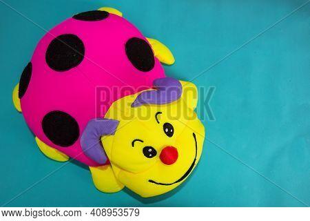 Soft Toy Ladybug Antistress. Pink Soft Toy Ladybug On A Blue Background. Children Playing And Having