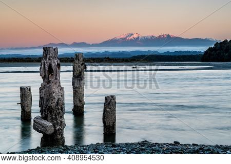 Long Exposure Sunrise With Mountain Background And Dilapidated Old Dock In The Foreground All Set In