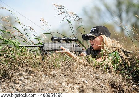 Female Army Soldier Shooting With Sniper Rifle. Woman With Weapon