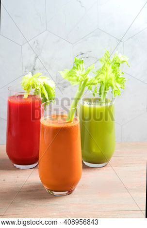 Three Glass Cups Of Natural Juices From Fresh Vegetables, Tomatoes, Celery And Carrots With Celery L