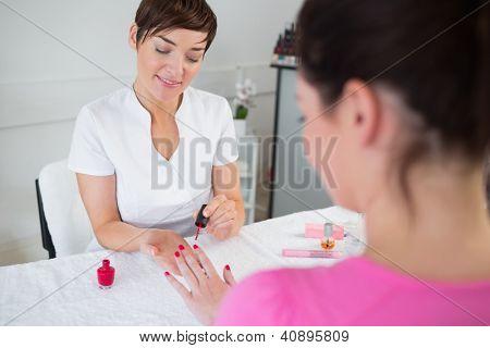 Nail technician applying nail varnish to finger nails at nail salon
