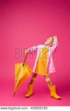 Full Length Of Surprised Girl In Raincoat And Rubber Boots Standing With Umbrella On Crimson.