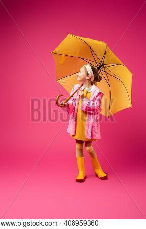 Full Length Of Positive Girl In Raincoat Standing Under Yellow Umbrella On Crimson.