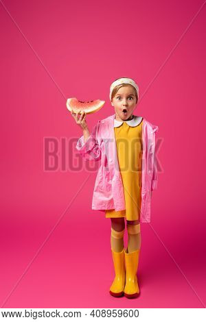 Full Length Of Shocked Girl In Raincoat And Rain Boots Standing With Watermelon On Crimson.