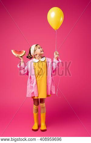 Full Length Of Cheerful Girl In Raincoat Holding Balloon And Sliced Watermelon On Crimson.