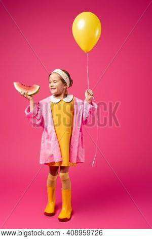 Full Length Of Happy Girl In Raincoat Holding Balloon And Sliced Watermelon On Crimson.