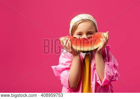Girl In Raincoat Covering Face While Holding Watermelon Isolated On Crimson.