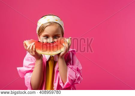 Girl In Raincoat Covering Face While Looking At Watermelon Isolated On Crimson.