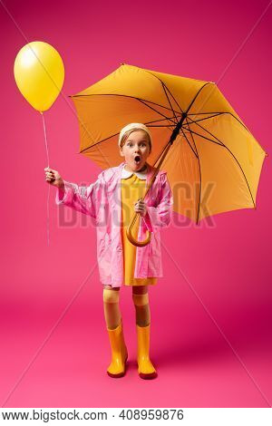 Full Length Of Amazed Child In Raincoat And Rubber Boots Holding Balloon And Yellow Umbrella On Crim
