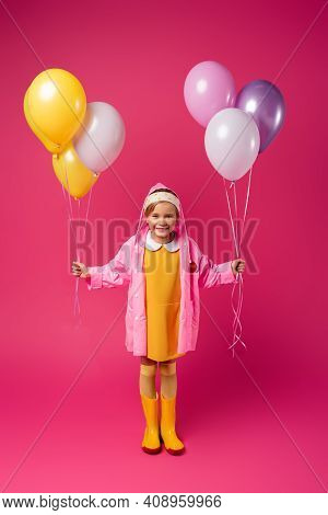 Full Length Of Happy Girl In Raincoat And Rubber Boots Holding Balloons On Crimson.