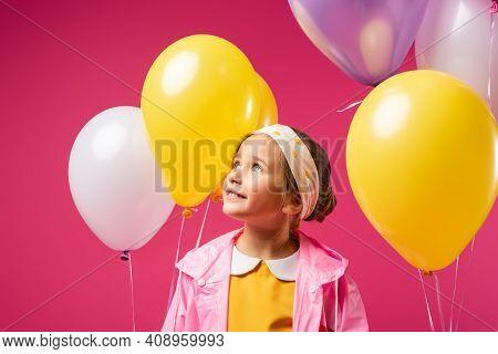 Happy Kid Looking Away Near Balloons Isolated On Crimson.