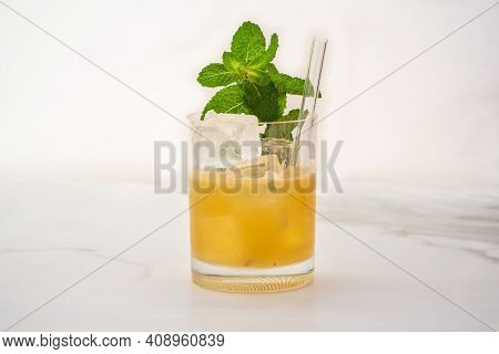 Mai Tai Cocktail And Tiki Drink Garnished With A Sprig Of Mint On White Background
