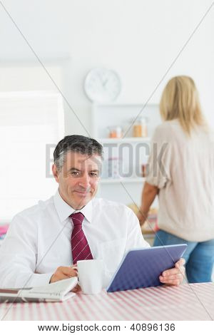 Smiling man with tablet pc and coffee at kitchen table before work