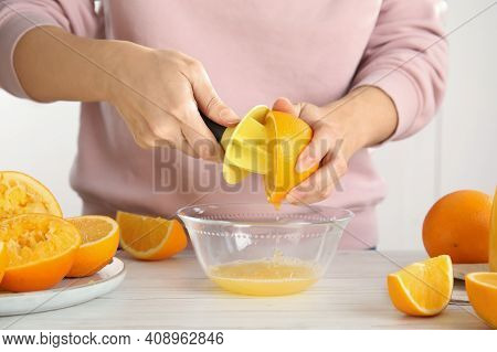 Woman Squeezing Orange Juice At Wooden Table, Closeup