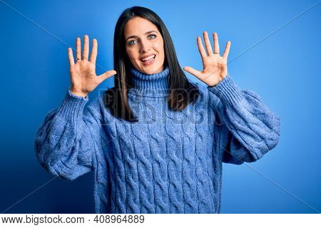 Young brunette woman with blue eyes wearing casual turtleneck sweater showing and pointing up with fingers number ten while smiling confident and happy.