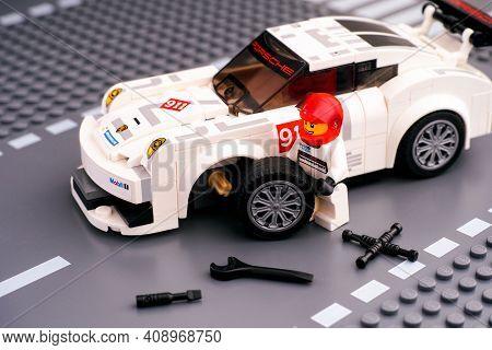 Tambov, Russian Federation - February 14, 2021 Lego Driver Minifigure Fixing Wheel Of White Porsche