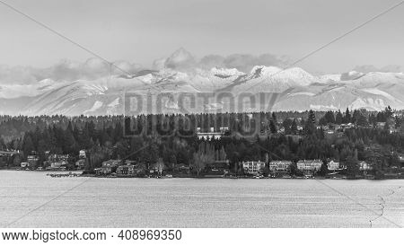 A View Of The Shoreline Of Bellevue, Washington With Mountains In The Distance.