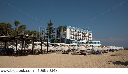 Famagusta, Cyprus - September 15 2016: Palm Beach With Beach Umbrellas And Tourists At A Modern Beac