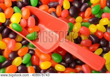 A Closeup View Of A Red Scoop In An Abundant Supply Of Jelly Bean Candy.