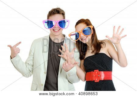 Young Happy Smiling Couple Wearing A Big Colored Glasses Having Fun On White Background