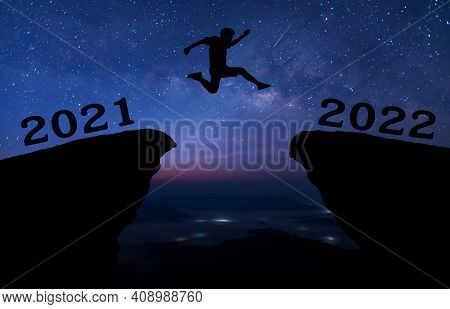 A Young Man Jump Between 2021 And 2022 Years Over Night Sky With Stars And Through On The Gap Of Hil