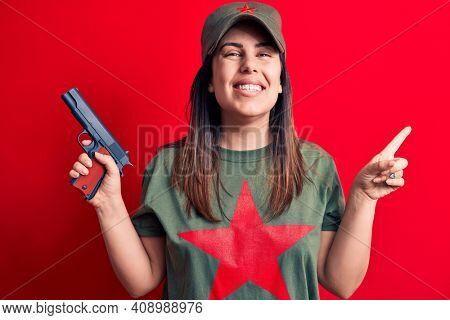 Young beautiful brunette woman wearing t-shirt with red star communist symbol holding gun smiling happy pointing with hand and finger to the side