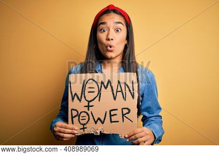 Beautiful activist asian woman asking for women rights holding banner with power message scared in shock with a surprise face, afraid and excited with fear expression