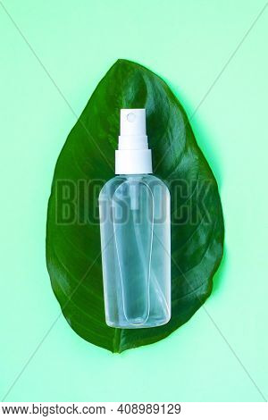 Hand Sanitizer On A Oval Leaf. Light Green Background. The Hand Sanitizer Has Become A Mandatory Ite