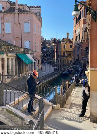 Venice, Italy, February 13, 2021 - Gondoliers wearing protective masks while waiting for a client during the Coronavirus crisis