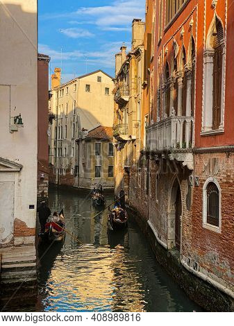 Venice, Italy, February 19, 2021 - Gondoliers taking tourists or couples on their honeymoon on a touristic tour