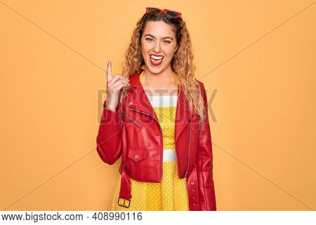 Young beautiful blonde woman pin-up with blue eyes wearing red sunglasses and jacket pointing finger up with successful idea. Exited and happy. Number one.
