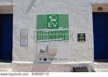 TILOS,GREECE - JUNE 15, 2019: A solar powered electric vehicle charging point on the seafront at Livadia. The unit can charge two vehicles at a time.