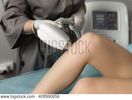 Beautician Removing Hair On Female Legs Using A Laser. Close-up Photo Of Cosmetologist Hand With Las
