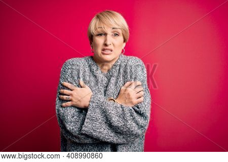 Young blonde woman with modern short hair wearing casual sweater over pink background shaking and freezing for winter cold with sad and shock expression on face