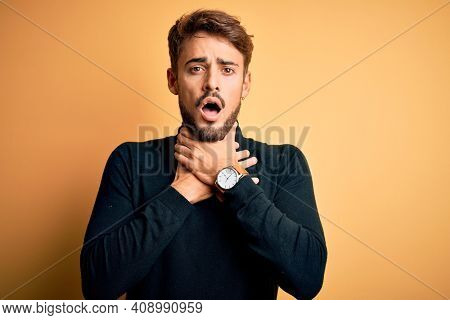 Young handsome man with beard wearing turtleneck sweater standing over yellow background shouting and suffocate because painful strangle. Health problem. Asphyxiate and suicide concept.