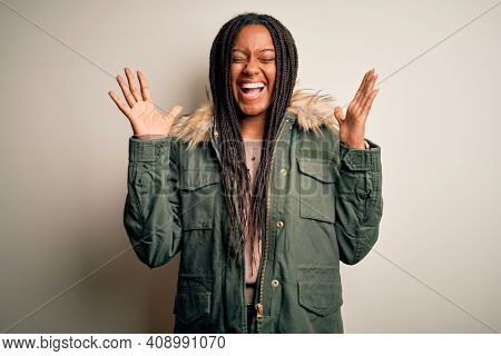 Young african american woman wearing winter parka coat over isolated background celebrating mad and crazy for success with arms raised and closed eyes screaming excited. Winner concept