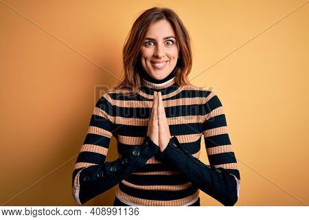 Young beautiful brunette woman wearing striped turtleneck sweater over yellow background praying with hands together asking for forgiveness smiling confident.