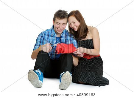 Smiling Teenage Girl And Boy Cutting Valentine Heart Out Of Red Paper With Scissors Over White Backg
