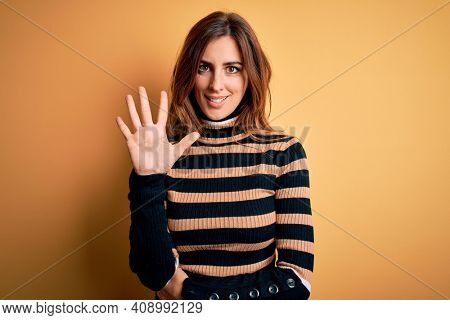 Young beautiful brunette woman wearing striped turtleneck sweater over yellow background showing and pointing up with fingers number five while smiling confident and happy.