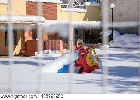 Winter Morning Snow Covered Empty Playground Of A Kindergarten With A Colorful Slide In Athens, Gree
