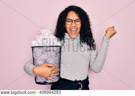 Young african american woman wearing glasses holding wastebasket with cumpled papers screaming proud and celebrating victory and success very excited, cheering emotion