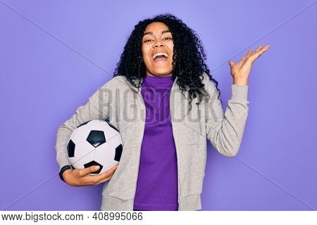 African american curly player woman playing soccer holding football bal over purple background very happy and excited, winner expression celebrating victory screaming with big smile and raised hands