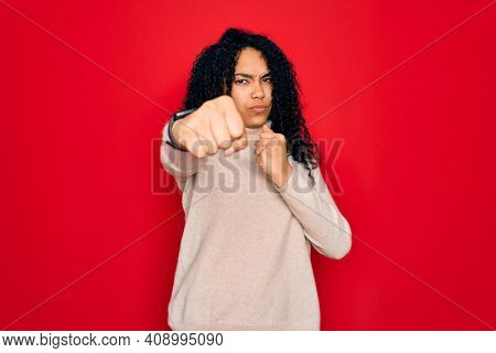 Young african american curly woman wearing casual turtleneck sweater over red background Punching fist to fight, aggressive and angry attack, threat and violence