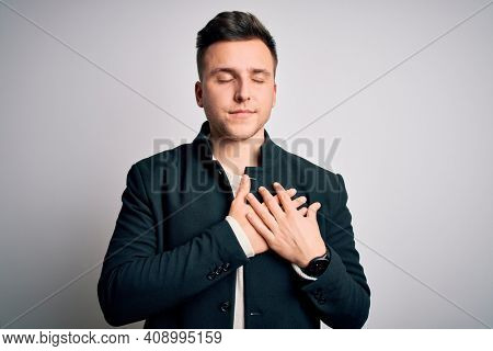 Young handsome business mas wearing elegant winter coat standing over isolated background smiling with hands on chest with closed eyes and grateful gesture on face. Health concept.