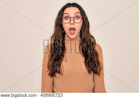 Young beautiful woman wearing casual turtleneck sweater and glasses over white background afraid and shocked with surprise expression, fear and excited face.