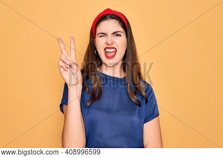 Young beautiful brunette woman wearing red lips over yellow background smiling with happy face winking at the camera doing victory sign. Number two.
