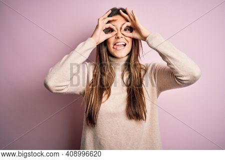 Young beautiful girl wearing casual turtleneck sweater standing over isolated pink background doing ok gesture like binoculars sticking tongue out, eyes looking through fingers. Crazy expression.