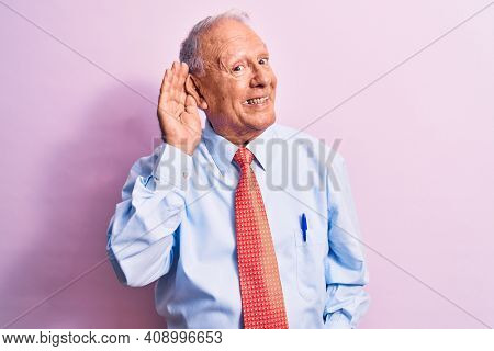 Senior handsome grey-haired businessman wearing elegant tie standing over pink background smiling with hand over ear listening and hearing to rumor or gossip. Deafness concept.
