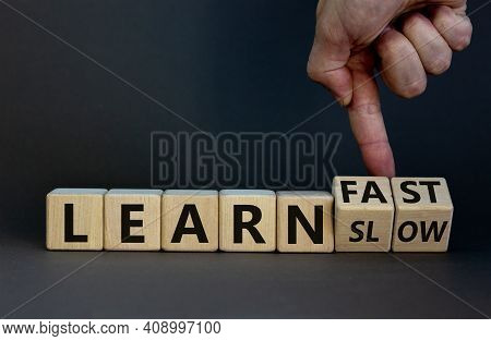 Learn Slow Or Fast Symbol. Businessman Turns Wooden Cubes And Changes Words 'learn Slow' To 'learn F