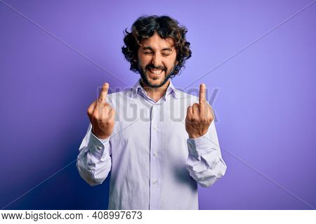 Young handsome business man with beard wearing shirt standing over purple background Showing middle finger doing fuck you bad expression, provocation and rude attitude. Screaming excited